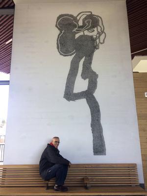 Modhir Ahmed framför sin bild av en kvinna med ett barn. Ett av nio storskaliga grafiska verk som visas i en permanent utställning i Falu resecentrum.