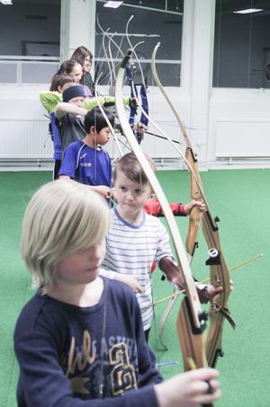 Ungdomarna i BSK Iggesund står uppradade för att fyra av pilar mot tavlorna.