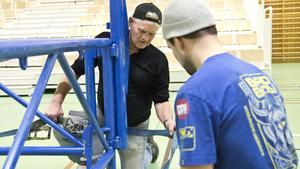 Håkan Pettersson och Jonas Andersson bygger upp en boxningsring i Ullvihallen när det senast var ett mästerskap i Köping. Den gången fick publiken bänka sig på teleskopläktaren som syns i bakgrunden, men i år blir det nobben. Foto/arkiv: David Eriksson.