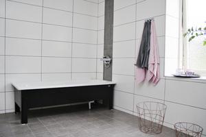 Rymligt badrum med både dusch och badkar. Ljuset leds in genom ett stort fönster på långsidan.
