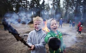 Rasmus Johansson och Hampus Kroon fäktas med facklor framför brasan på Högliden.
