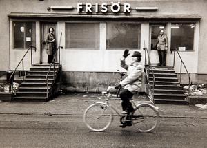 Hallstavik cirka 1975. Karl-Erik Eriksson cyklar förbi Iris och Lennart Larssons frisörsalong på Carl Wahrens väg.