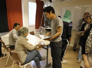 Meisam Rezaei delar ut tidningen som heter Ivik-posten till Nadia Shaukat.