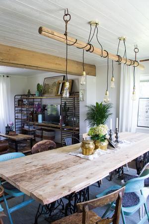 Även matbordet i vardagsrummet har paret gjort själva. Som ben användes underreden från gamla symaskinsbord. Runt bordet står både gamla och nya och gamla stolar.