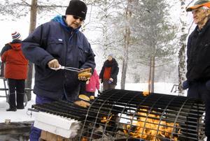 Gemenskap vid brasan. Alf Djupman och Arne Persson har ordnat med korvgrillning i byn.