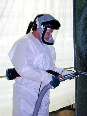 Foto: ULF GRANSTRÖM Skyddad sanerare. Lars-Olov Lindberg iförd overall och ansiktsskydd håller på att skära ut en fog på stenväggen på Hagaskolan.