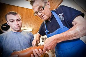 Så här syr man fast sulor på skorna. Jan-Erik Melkersson visar Gabriel Voicu. Foto: Emma Bergstrand
