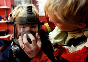 David Hägglund provar en gasmask. Han andas i den och kan ge oss ett rungande hej bakom masken.