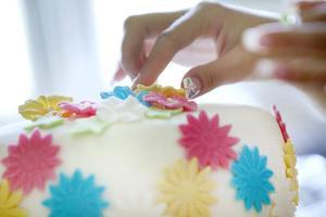 Tårtan är täckt av en deg gjord på smälta marshmallows och florsocker.Dekorationerna är gjorda av färgad deg där Elin stansat ut blommorna.