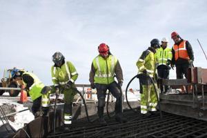 Sex man jobbade med betongen under tisdagen. När man kommit så här långt är det mesta av arbetet gjort, nu gäller det bara att styra betongen på rätt plats och arbeta ur luften ur den färdiga betongen. Armeringsjärnen kommer förbockade från en fabrik i Polen och sätts ihop på plats efter ritningar.