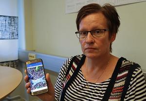 Jeanette Rönnberg visar upp en av bilderna hon tog på de fem döda katter som hon hittade i skogen.
