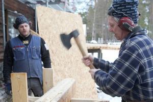 Åke Gustafsson täljer draget som är till för att det ska bli tätt mellan stockarna. Örjan Näslund har försågat med motorsåg.
