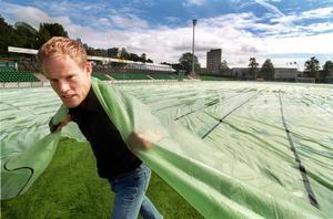 2000. GIF Sundsvalls nyförvärv Joel Cedergren hjälper till och drar över skyddsplasten över gräsmattan på IP.
