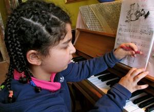 Shaili antecknar sin pianoläxa inför kommande veckas lektion,iförd sin nya frisyr för dagen.