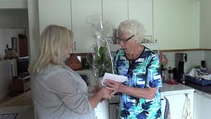 Ann-Marie Åhlander lämnar över de pengar, och en blomma, som facebookgruppen