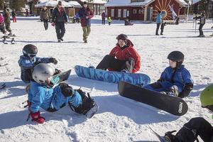 Andreas Sjöbeck lär barnen hur de skall ta sig upp i stående läge med snowboard.