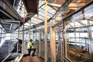 Henrik Eriksson från Östersunds Glasmästeri monterar lister på glaspartierna till den nya glaspaviljongen i Badhusparken. Paviljongen blir ett inglasat uterum med infravärme där man sitter med ytterkläder på under årets kalla månader.