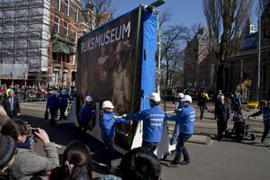 Arbetare drar Rembrandts mästerverk Nattvakten till dess plats i det nyrenoverade museet.