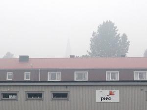 Röken ligger tät i luften i Norberg – kyrktornet som skymtar bakom brandstationen är knappt synligt.