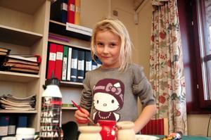 gör en LJUSSTAKE. Tyra Jernberg, 6 år, från Ytterharnäs målade en planka röd. När färgen torkat skulle hon klistra på ljushållare.
