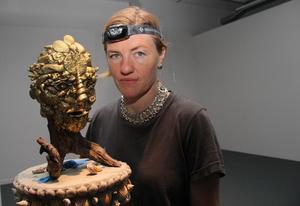 Den guldfärgade masken är samma figur som det orakel som sitter på en snäcka i utställningen.
