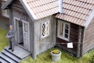 HÄLLS I HEDESUNDA. Här bodde Niclas Flodbergs morfars morfar, soldaten och postiljonen Anders Häll med fru och nio barn. Huset är förändrat i dag, men Niclas har tagit mått på huset och byggt en modell efter sin mammas beskrivning av hur hon mindes det från barndomen. Inuti är kökets interiör rekonstruerad med hjälp av fotografier och minnesbilder. Tapeten som syns på ett foto har Niclas återskapat i datorn, liksom järnspis och en del möbler. Men husets väggar är förseglade och kökets alla små detaljer kan bara anas innanför gardinerna. Klädstrecket är ett hårstrå...