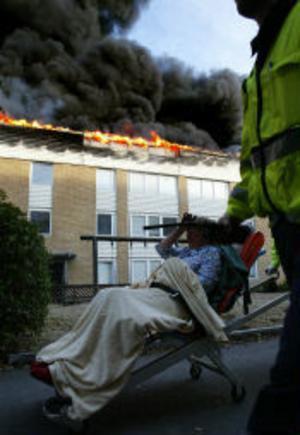 En kvinna evakueras från det brinnande huset. Ingen kom dock till allvarlig skada under gårdagens brand i Skönsberg.