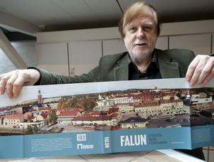 Bokens redaktör Örjan Hamrin - som både skrivit texter och fotograferat - vecklar ut bokens omslag, Holmtorget på nästan en meter bild.