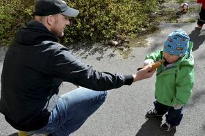 Leon Svensson 1 år delar en korv med bröd tillsammans med pappa.