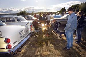 Intill en gulvit Chevrolet Bel Air från 1958 sitter Rickard Lindström och Kicki Rengart vid det uppfällda campingbordet.