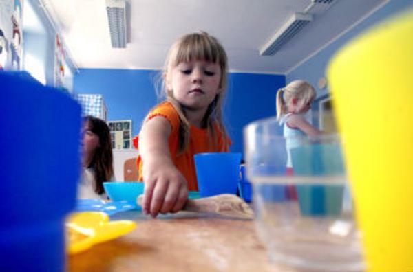 Dags för fika. Anna, fyra år, dukar på sin alldeles nya förskola, personalkooperativet Optimus, vid Sidsjön.