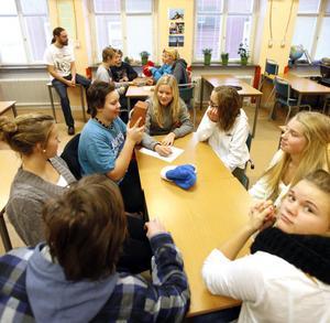 """Idékläckning. När Ung Företagsamhet hälsade på i klass 8A fick klassen i uppdrag att komma med så många kreativa idéer som möjligt om vad man kan använda en tegelsten till, förutom att bygga hus. """"Pennhållare och träningsredskap, typ hantlar"""", föreslår Albin Molander medan han känner på tegelstenen. Vid bordet sitter även, från vänster, Erik Sjödén, Elisabeth Eriksson, Heidi Axelsson, Linnea Persson, Ellen Nilsson och Julia Wiberg."""