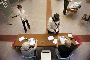 Förtidsröstningen blir allt populärare. Här tar förtidsröstmottagarna Britt Thureson och Owe Carlsson på Stadsbiblioteket emot röstsedlar och röstkort av en väljare. Foto:Stina Rapp