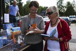 Eva Ludvigsen signerar ett exemplar till Ulla-Britt Lundin, som faktiskt har en egen karaktär i form av moster Linda i