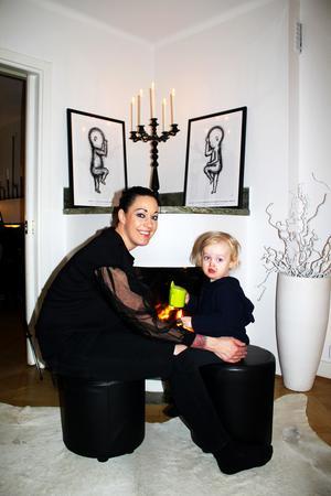 Catharina Molin och sonen Maximilian framför den öppna brasan i hemmet i centrala Västerås. Ovanför spisen hänger barnens födelsetavlor.