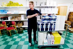 En vagn kommer lastad. Tidigare var det vårdpersonal som ansvarade för att hålla ordning i avdelningarnas förråd av förbrukningsvaror. Nu har serviceenheten tagit över. Lennart Godin och hans kollegor går regelbundet runt och fyller på av det som saknas och beställer nytt. Den här vagnen – som snart är fullastad – ska upp till BB.