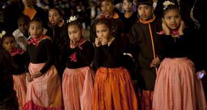 Unga tjejer som har dansat traditionella danser väntar på vad som ska följa under festivalen.