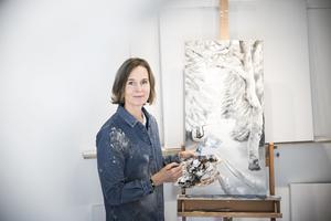 Sofia Ohlsén, vid en halvfärdig tavla, i sin ateljé.