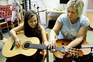 Lärorikt. Ella och Carina Fransson lärde sig att ta toner både på gitarr och stråkinstrument under tisdagskvällen.