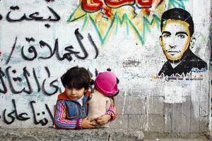 Graffiti , kärlek och politik.  Treåriga Wader framför martyrporträttet av hennes pappa, 2007.