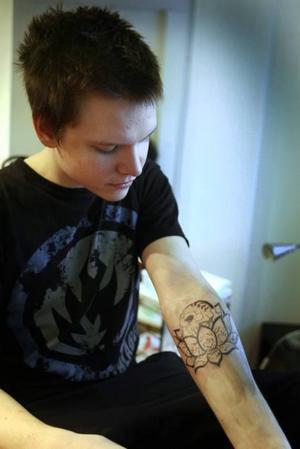 """LOTUSBLOMMA MED DÖdSKALLE. Mattias får sin andra tatuering. Det blir en lotusblomma med en dödskalle i. """"Jag har hittat motivet på internet. Den har ingen speciell betydelse för mig, utan jag valde den för att den är snygg""""."""