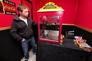 På väg in i biosalongen passerar man en kiosk med popcornmaskin, läskkyl och en disk med godis.