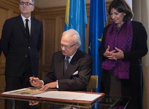 Kung Carl XVI Gustaf skriver i en gästbok vid ett besök i Paris, som överses av André Vallini och Anne Hidalgo.