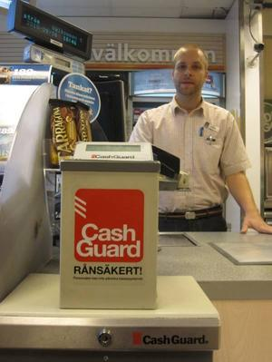 INLÅSTA PENGAR. Fredrik Eriksson, säljare på Statoil i Hagaström, säger att de har haft ett slutet system för kontanter så länge han har jobbat där, i tio år. Under den tiden har de varit förskonade från rån.