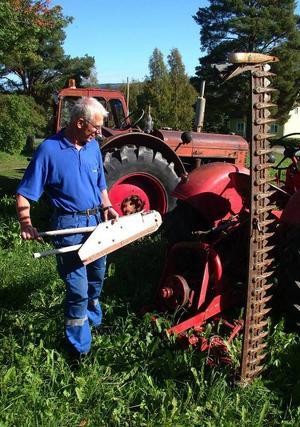 En International slåttermaskin av ädelt snitt sitter monterad på en av Everts traktorer.