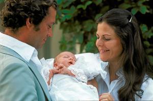 Kung Carl XVI Gustaf och drottning Silvia visar upp nyfödda prinsessan Victoria för media på Solliden på Öland 1:a augusti 1977. Prinsessan har hunnit bli tre veckor gammal.