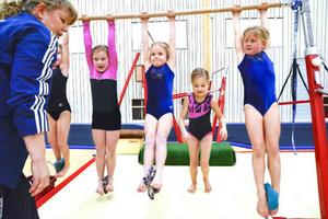 Här är det tjejerna i träningsgruppen Artistisk gymnastik 1 som tränar grunderna i barr under påseende av My Andersson.