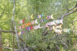Fiskstim. Mitt i skogen simmar de här regnbågsfärgade fiskarna förbi. Gjorda av Frida Larsson.