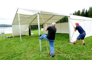 Willy Olsson och Kenneth Svedlund tar i för kung och fosterland när den ska dra montera tältdukarna på kiosktältet.