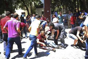 Människor hjälper skadade efter en självmordsattack i den turkiska staden Suruç, där ett 30-tal personer dödats och ett hundratal människor har skadats.